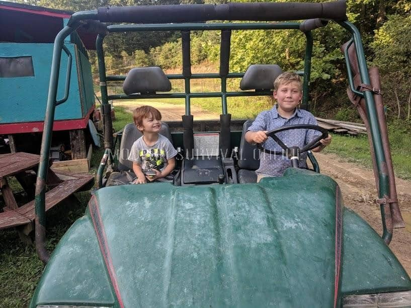 boys driving an atv on the homestead