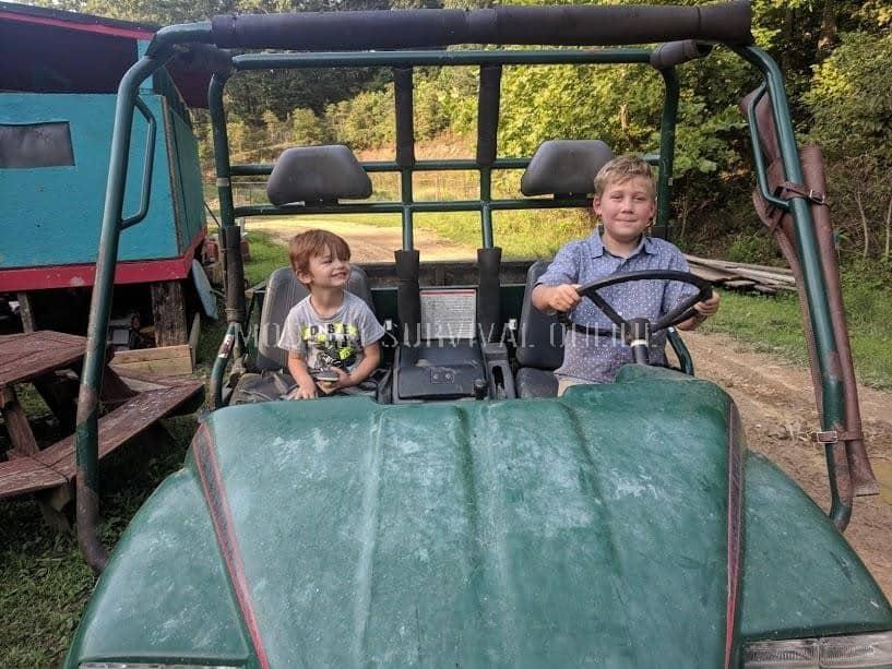 boys driving an atv on the homestead