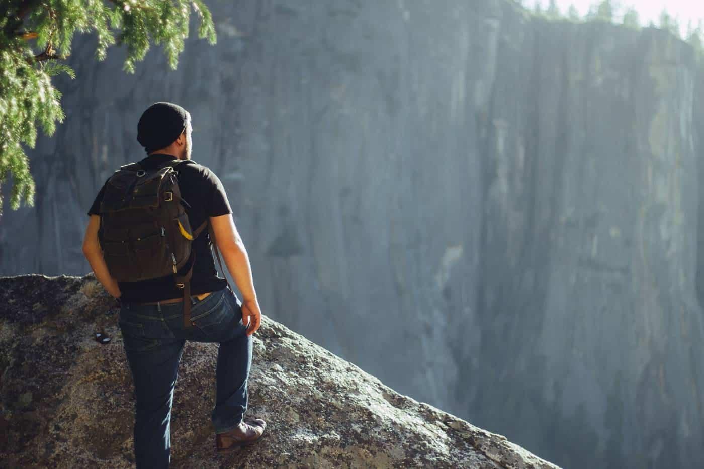 man wearing dark colored backpack