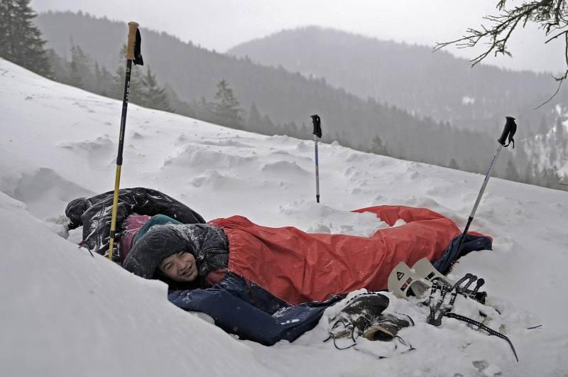 man in bivvy bag on mountain