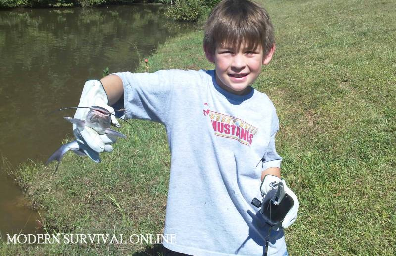 boy with caught fish in fishing rod